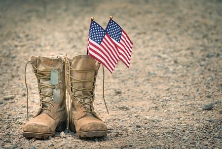 Foto de Old military combat boots with dog tags and two small American flags. Rocky gravel background with copy space. Memorial Day or Veterans day concept. - Imagen libre de derechos