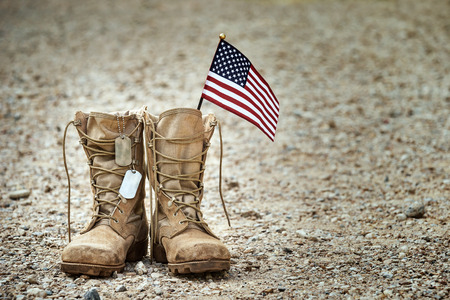 Foto de Old military combat boots with dog tags and a small American flag. - Imagen libre de derechos