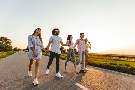 Foto de Company of happy young stylish guys hold their hands and walk on a country road on a sunny day - Imagen libre de derechos