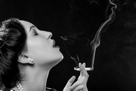 Photo pour sensual young woman smoking joint on black background, monochrome - image libre de droit