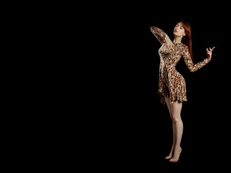 Foto de barefoot girl in dress dancing on black background with copy space - Imagen libre de derechos