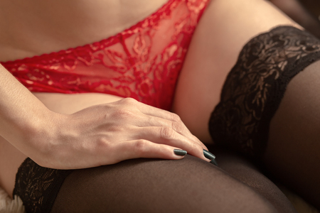 Foto de beautiful female slim body in red panties and stockings closeup - Imagen libre de derechos