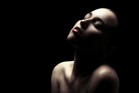 Photo pour sensual aroused woman with bare shoulders, closed eyes on black background - image libre de droit