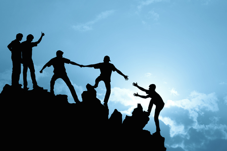 Foto de Group of people on peak mountain  climbing helping team work , success concept - Imagen libre de derechos