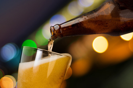 Foto per Motion of beer pouring from bottle into glass on bokeh light night background drinking alcohol celebration concept design - Immagine Royalty Free