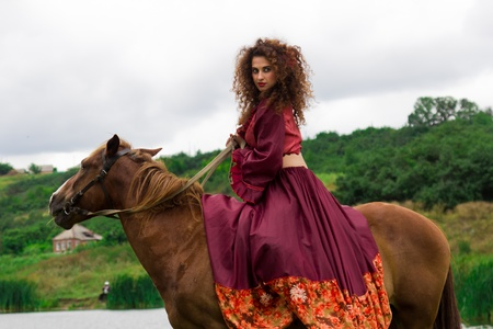 Beautiful gypsy girl riding a horse in the field