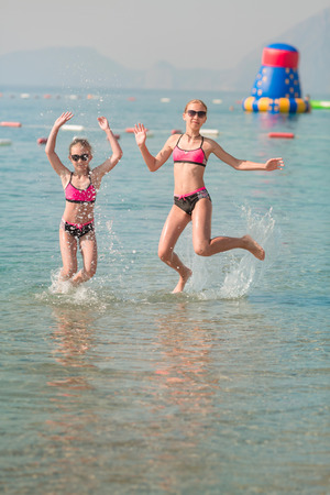 Photo for Happy young girls at the seaside sunbathing, having fun - Royalty Free Image