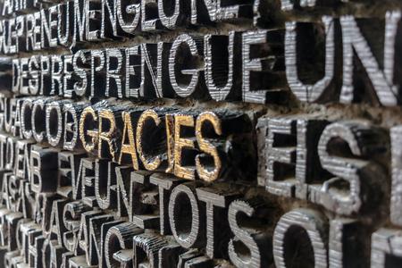 Foto de Detail with word Gracies (Thanks in catalan) on the bronze door of Passion facade of Sagrada Familia in Barcelona. The gospel doors contain text from the New Testament depicting the Passion of Christ. - Imagen libre de derechos