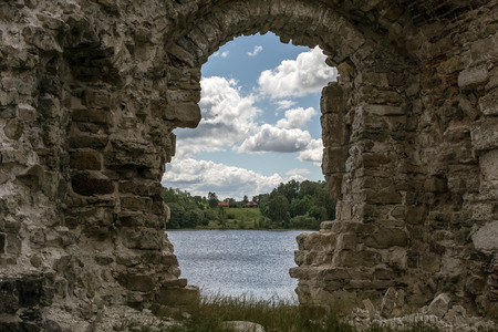 Photo for River and clouds through ruins of Koknese Castle - one of the largest medieval castles in Latvia. Construction of hydroelectric dam in 1965 partially submerged the castle and surrounding valley. - Royalty Free Image