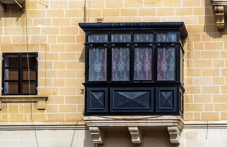 Foto de Traditional Maltese enclosed wooden balcony painted in black with white lace curtains in Cospicua (Bormla), Malta. Authentic Maltese urban scene. - Imagen libre de derechos