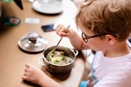 Photo pour Blonde boy with big glasses having lunch in the restaurant. - image libre de droit