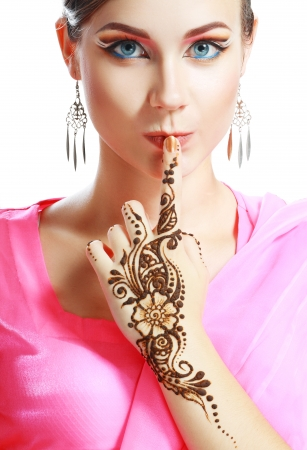 Beautiful girl face with perfect arabian make up with hand with detail of henna being applie mural