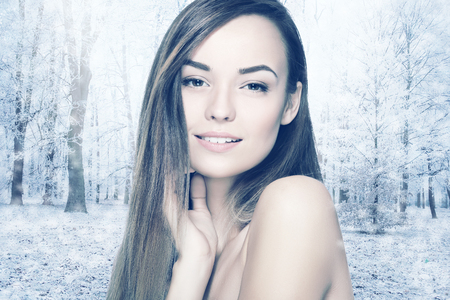 Head and shoulders of young woman with eyes closed over winter forest. Cryotherapy and cryosauna concept