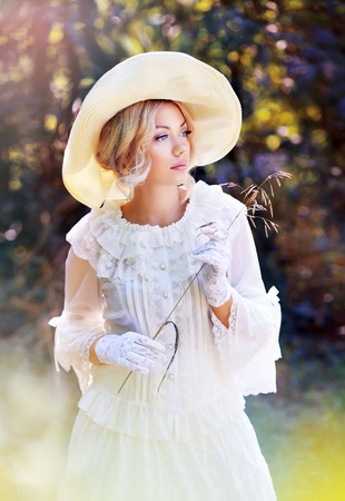 Photo for portrait of beautiful woman in victorian age dress and fancy hat walking outdoor - Royalty Free Image