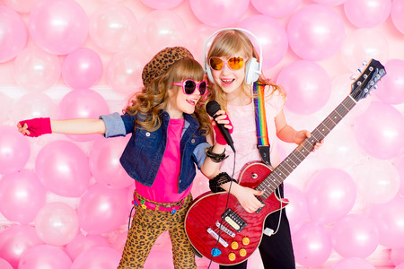 Photo for two little girl singing a song with a microphone and a guitar on a background of pink balloons - Royalty Free Image