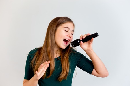 Photo for Girl singing with a microphone - Royalty Free Image