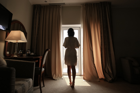 Foto de Beautiful young woman, silk bathrobe, standing by the window, natural light, toned - Imagen libre de derechos