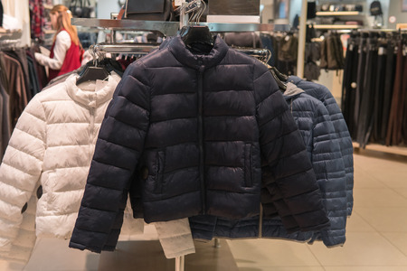 Foto de Row of white, black and gray down coats on the rack, clothing shop interior on background. Warm winter wear in fashion store - Imagen libre de derechos