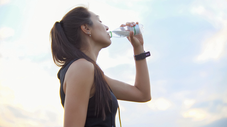 Photo pour Young beautiful sportswoman drinks water from a bottle outdoors after training - image libre de droit