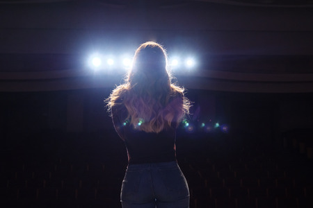 Photo for unrecognizable singer standing on stage at microphone in night club, back view - Royalty Free Image