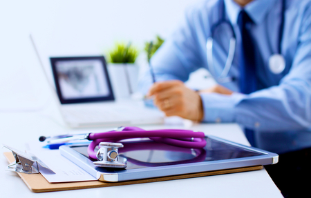 Foto de Doctor at work, close up of male doctor typing on a laptop. - Imagen libre de derechos