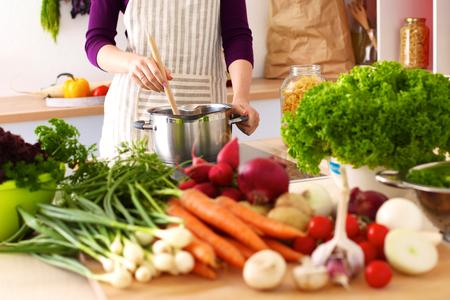 Foto de Young Woman Cooking in the kitchen. Healthy Food. - Imagen libre de derechos
