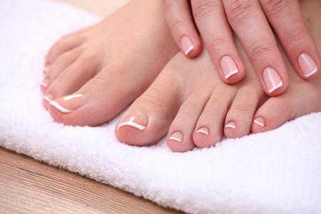 Foto de Closeup photo of a beautiful female feet with red pedicure isolated on white. - Imagen libre de derechos