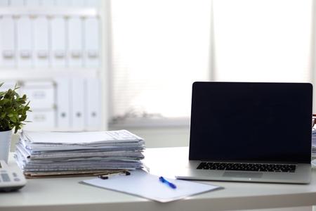 Photo pour Laptop with stack of folders on table on white background. - image libre de droit