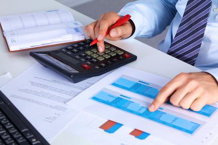 Photo pour Big boss checks calculations on a calculator. - image libre de droit