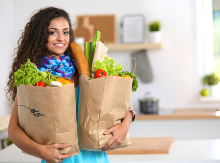 Photo pour Young woman holding grocery shopping bag with vegetables .Standing in the kitchen - image libre de droit