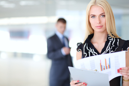 Photo pour Business woman standing in foreground with a folder in her hands . - image libre de droit