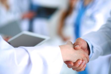 Foto de Young medical people handshaking at office . - Imagen libre de derechos