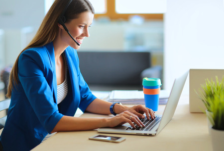 Foto de Portrait of beautiful business woman working at her desk with headset and laptop. - Imagen libre de derechos
