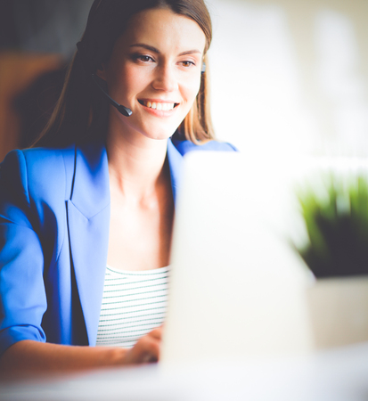 Photo for Portrait of beautiful business woman working at her desk with headset and laptop. - Royalty Free Image