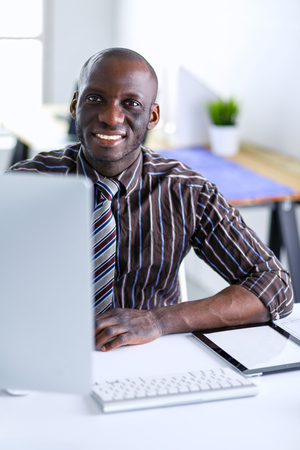 Photo for Handsome afro american businessman in classic suit is using a laptop and smiling while working in office - Royalty Free Image