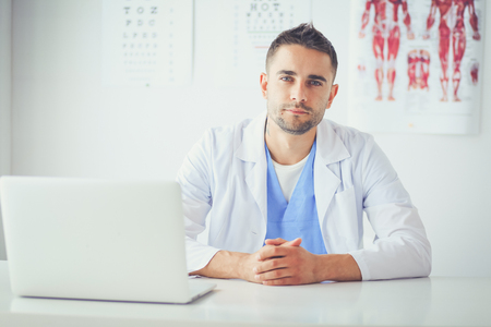 Photo pour Portrait of a male doctor with laptop sitting at desk in medical office. - image libre de droit