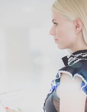 Foto de Business woman standing in foreground with a tablet in her hands - Imagen libre de derechos