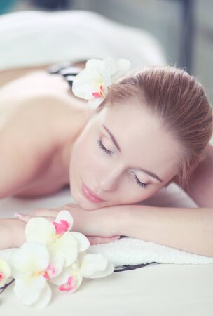 Photo for Young woman enjoying a hot rock massage in a spa salon and white flower on her head - Royalty Free Image