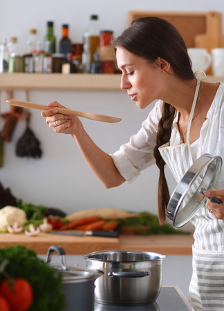 Photo for Cooking woman in kitchen with wooden spoon. - Royalty Free Image