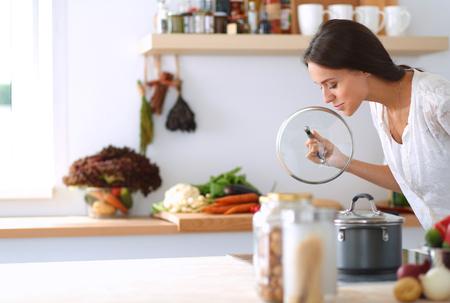 Foto de Young woman standing by the stove in the kitchen . - Imagen libre de derechos
