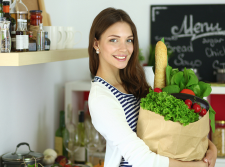 Photo pour Young woman holding grocery shopping bag with vegetables - image libre de droit
