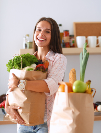Photo pour Young woman holding grocery shopping bag with vegetables . - image libre de droit