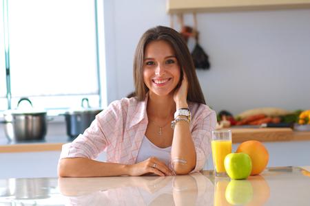 Foto de Young woman sitting near desk in the kitchen . - Imagen libre de derechos