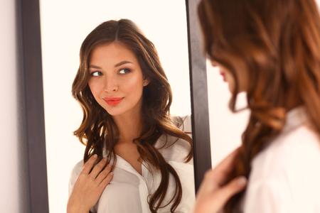 Foto de Young woman looking herself reflection in mirror at home. - Imagen libre de derechos