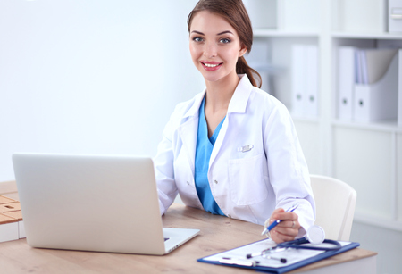 Photo for Beautiful young smiling female doctor sitting at the desk and writing. - Royalty Free Image