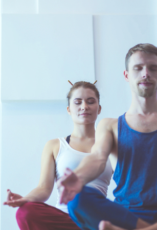 Photo pour Young healthy couple in yoga position on white background - image libre de droit