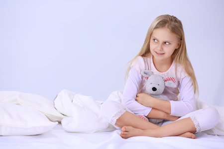 Foto de Little girl in the bedroom is sitting on the bed. Little girl is wearing a pajamas and sitting in bed . - Imagen libre de derechos