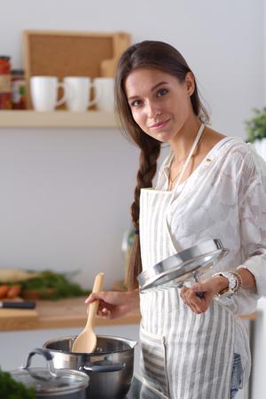 Foto für Cooking woman in kitchen with wooden spoon. Cooking woman - Lizenzfreies Bild