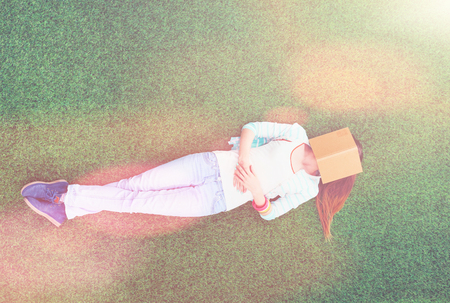 Photo for Beautiful young woman lying on the green grass - Royalty Free Image