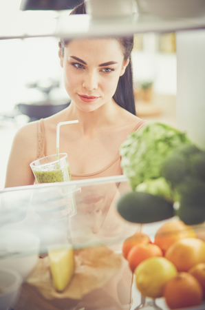 Photo for Smiling woman taking a fresh vegetable out of the fridge, healthy food concept - Royalty Free Image